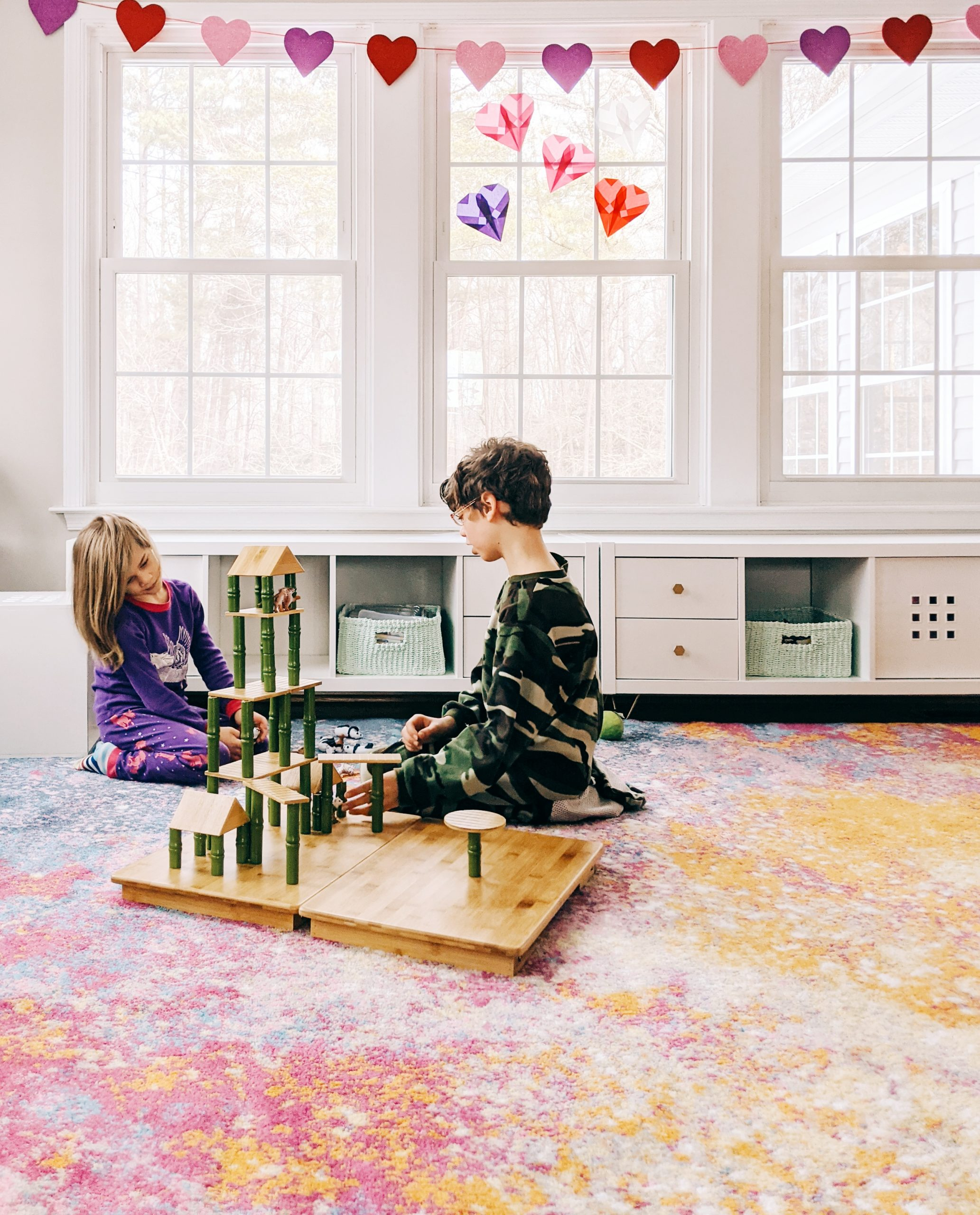 Two children play with building toys in a bright playroom. There is a heart garland over the window, and paper origami hearts in the windowpanes as sun-catchers.