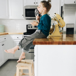 child sits on a kitchen counter licking a batter beater. the kitchen is bright and airy, freshly remodeled.