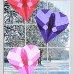 Three folded origami paper hearts hang in a window with sun shining through them. Outside the window it is snowy. The light is shining through the hearts.