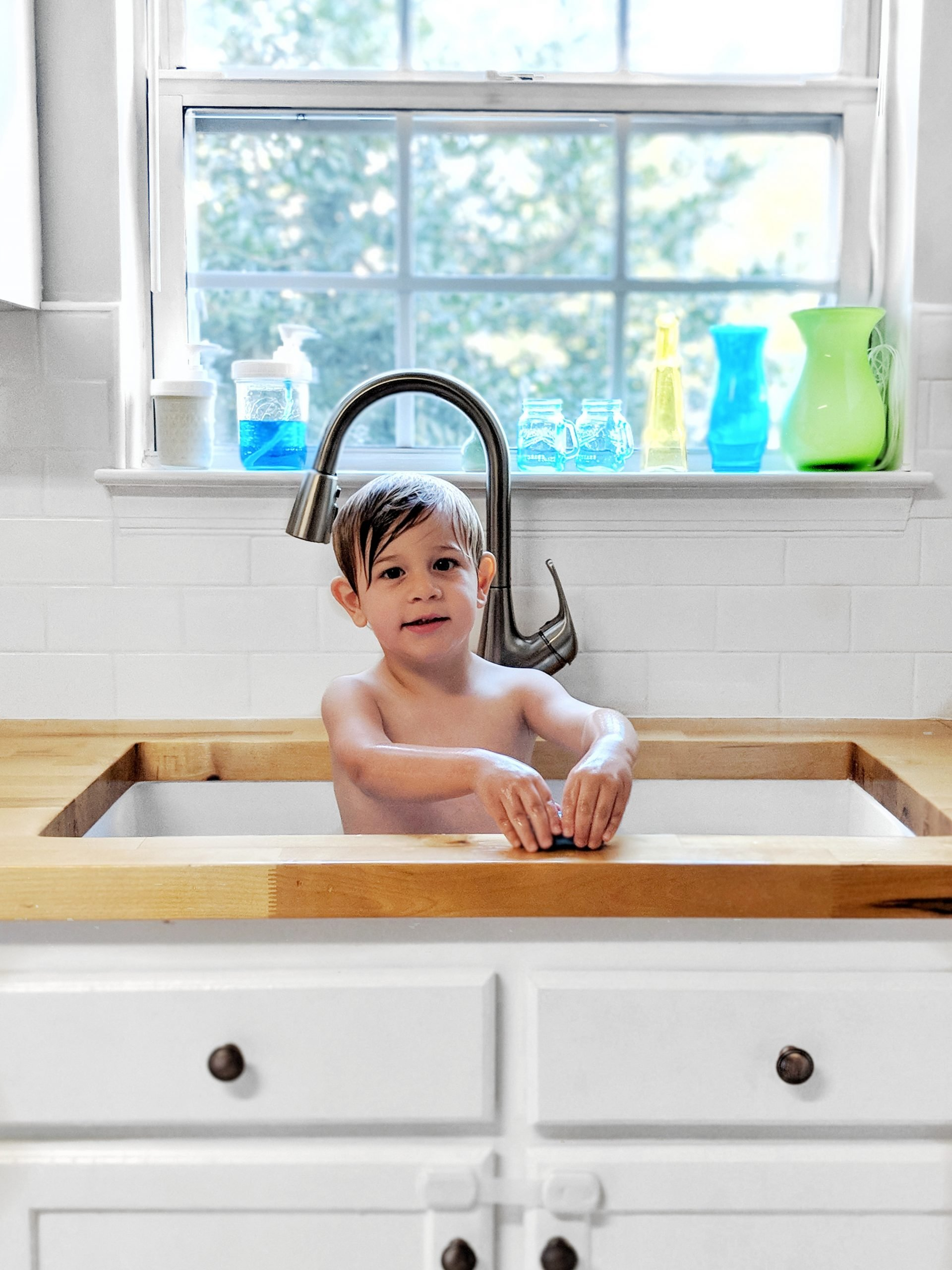 best part of the diy kitchen remodel - switching to a huge new single basin sink. a child takes a bath in the gigantic white sink. butcher block counters and subway tile backsplash