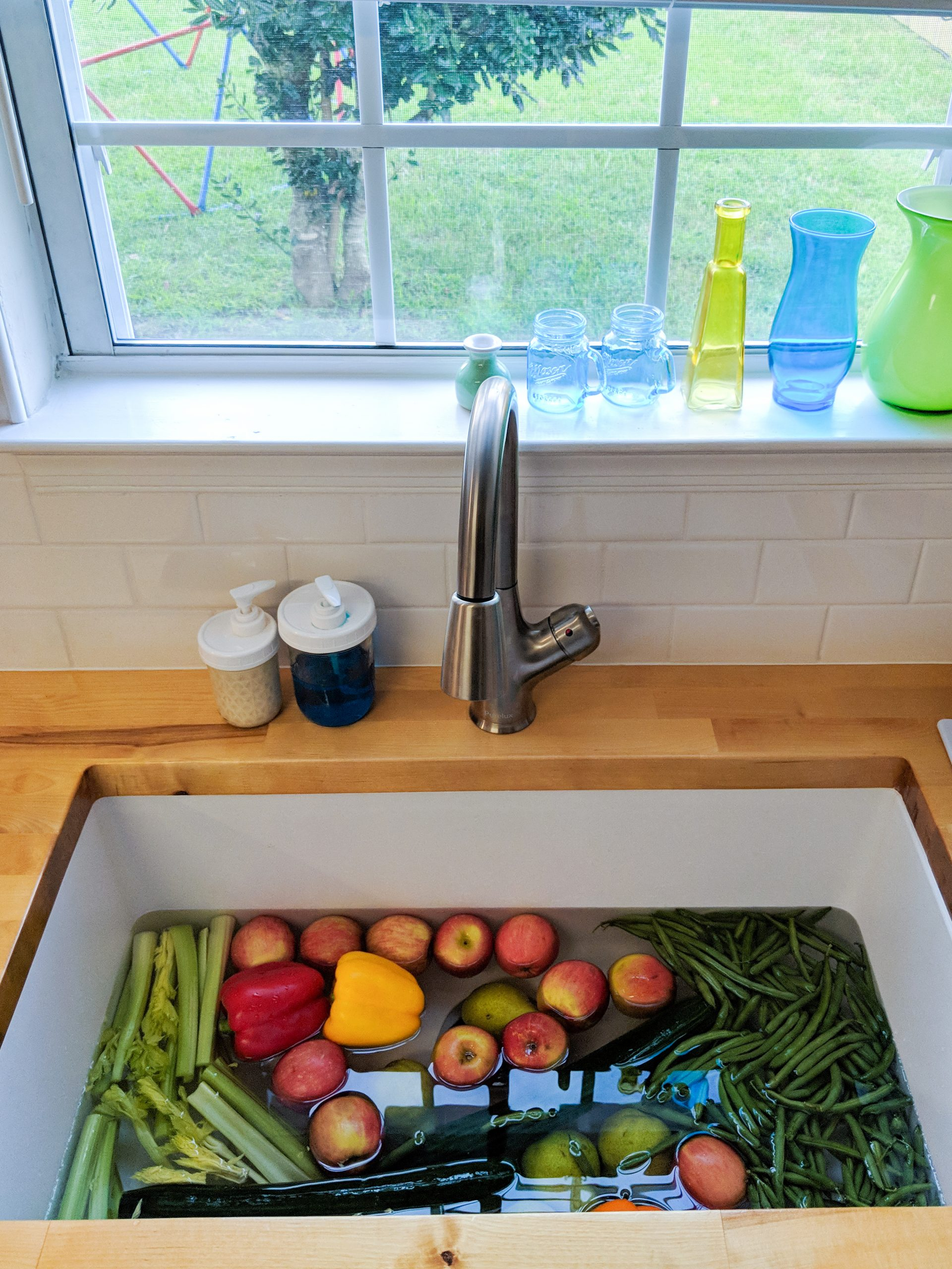 lots of fruit and vegetables soak in a gigantic white sink, surrounded by butcher block counters and subway tile backsplash.