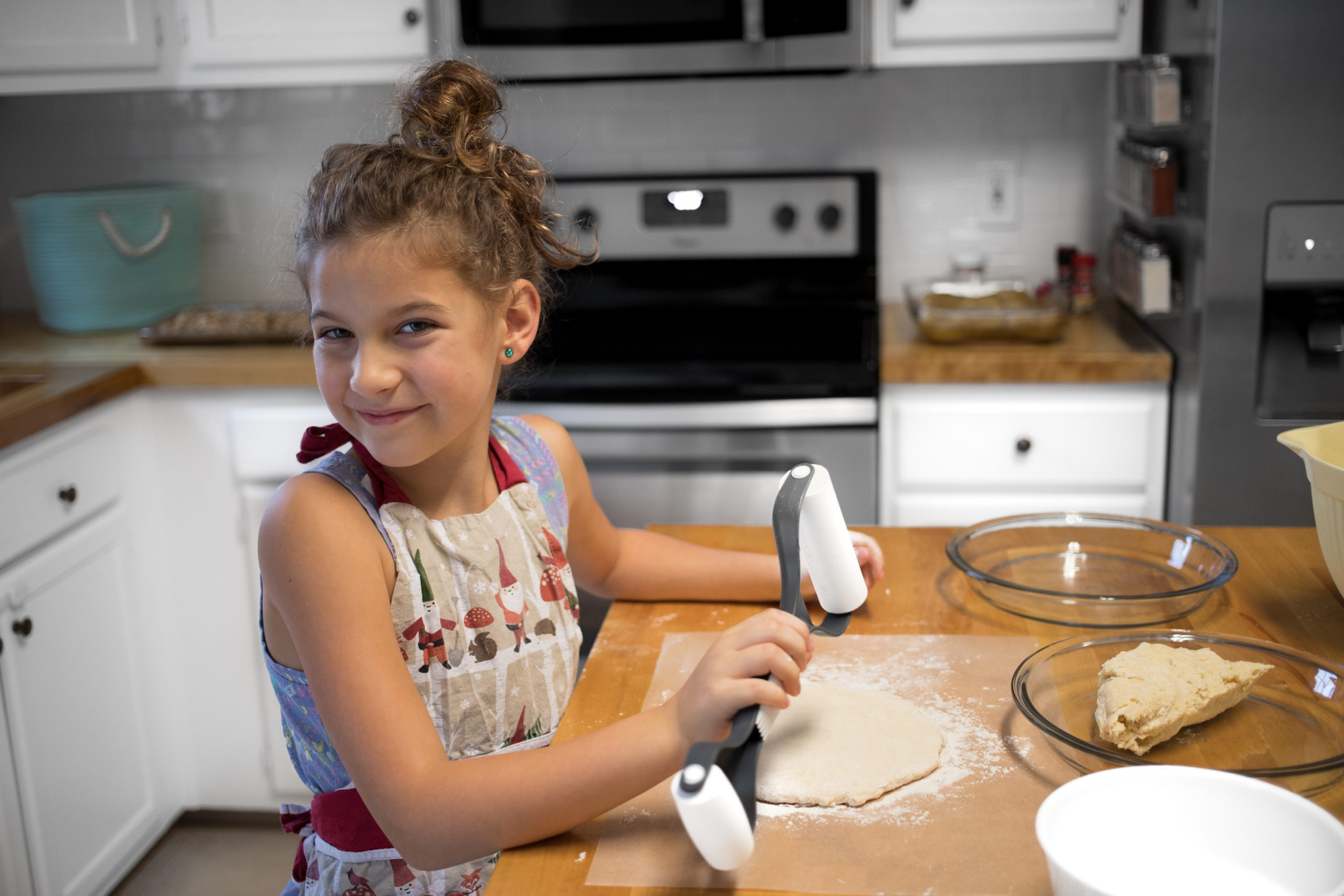 child in an apron rolling dough on butcher block kitchen counters
