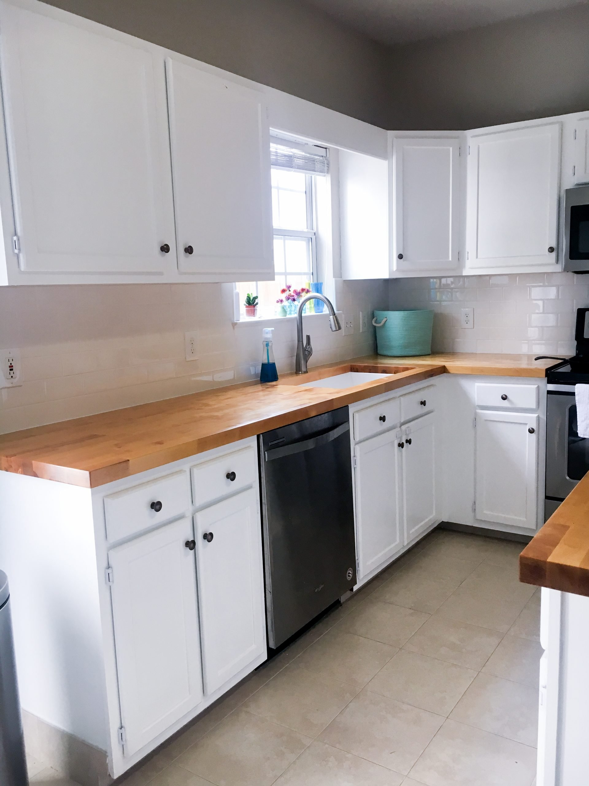 a simple way to update cabinets can be as easy as replacing dark hinges for white ones. cute kitchen with white cabinets, subway tile backsplash, butcher block counters, tile floor, stainless steel appliances.