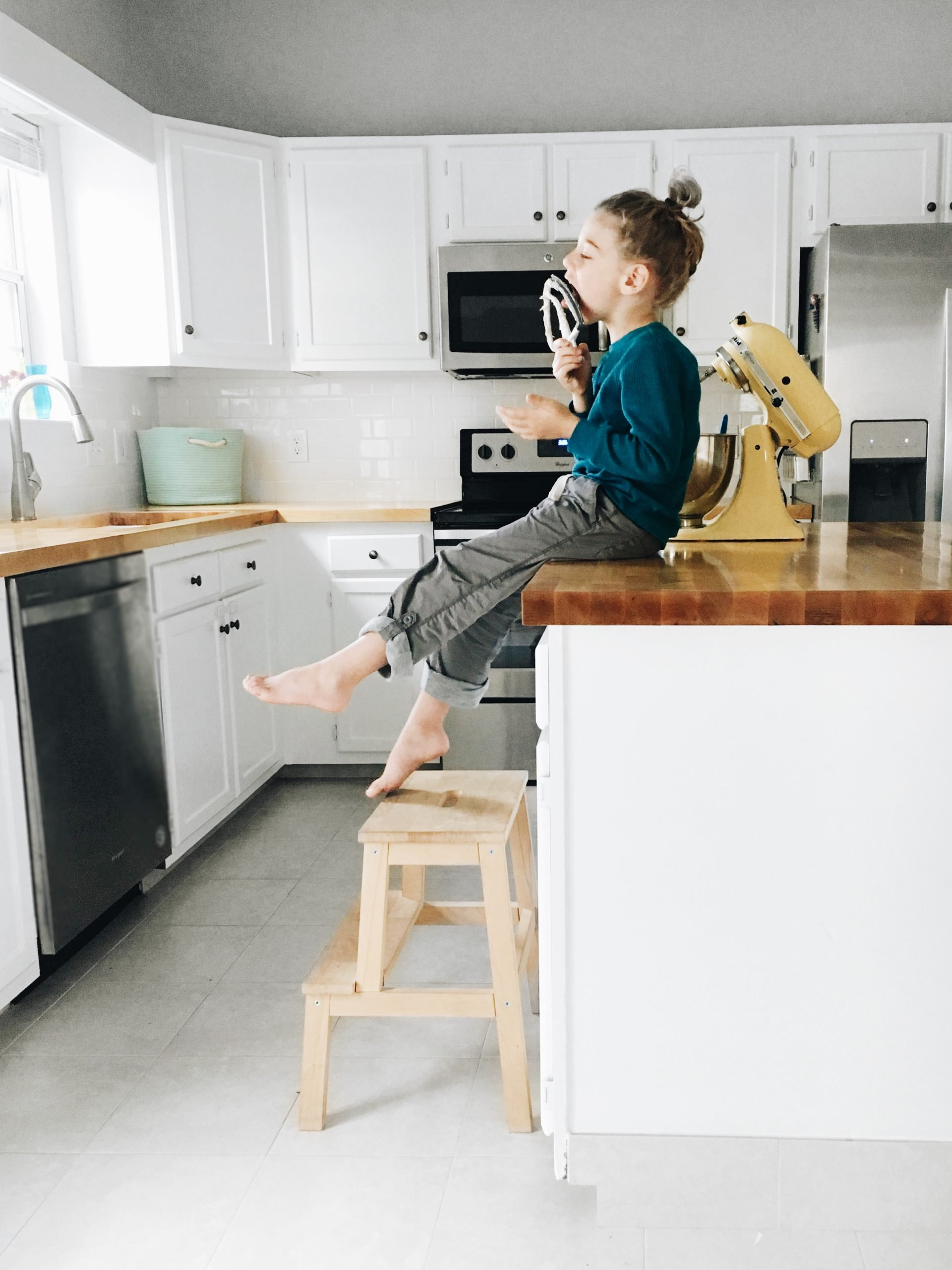 after a diy mini kitchen remodel, a child sits on a butcher block counter and licks a mixer beater.