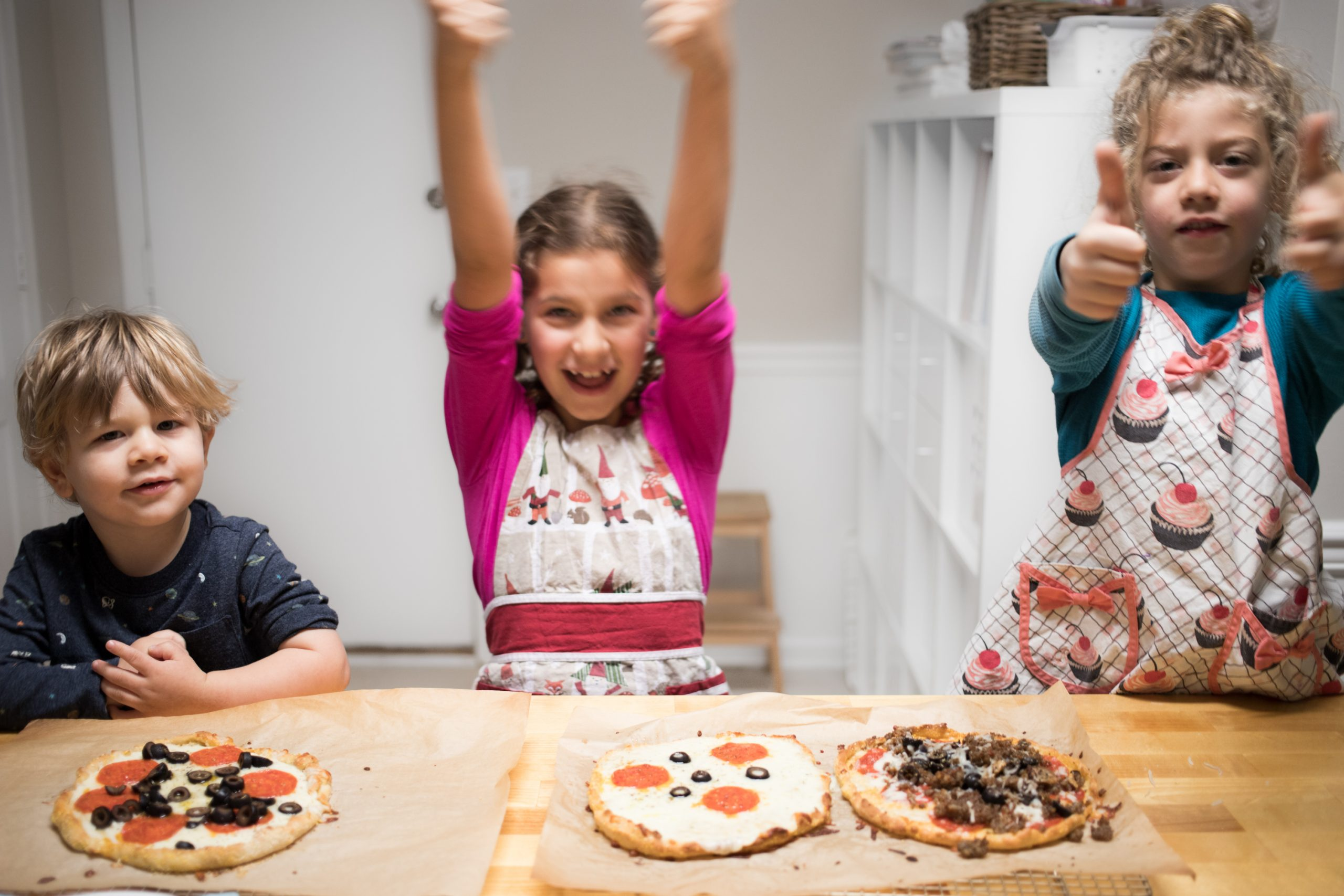 three children smile, sitting at a butcher block kitchen counter, with make-your-own-pizzas in front of them