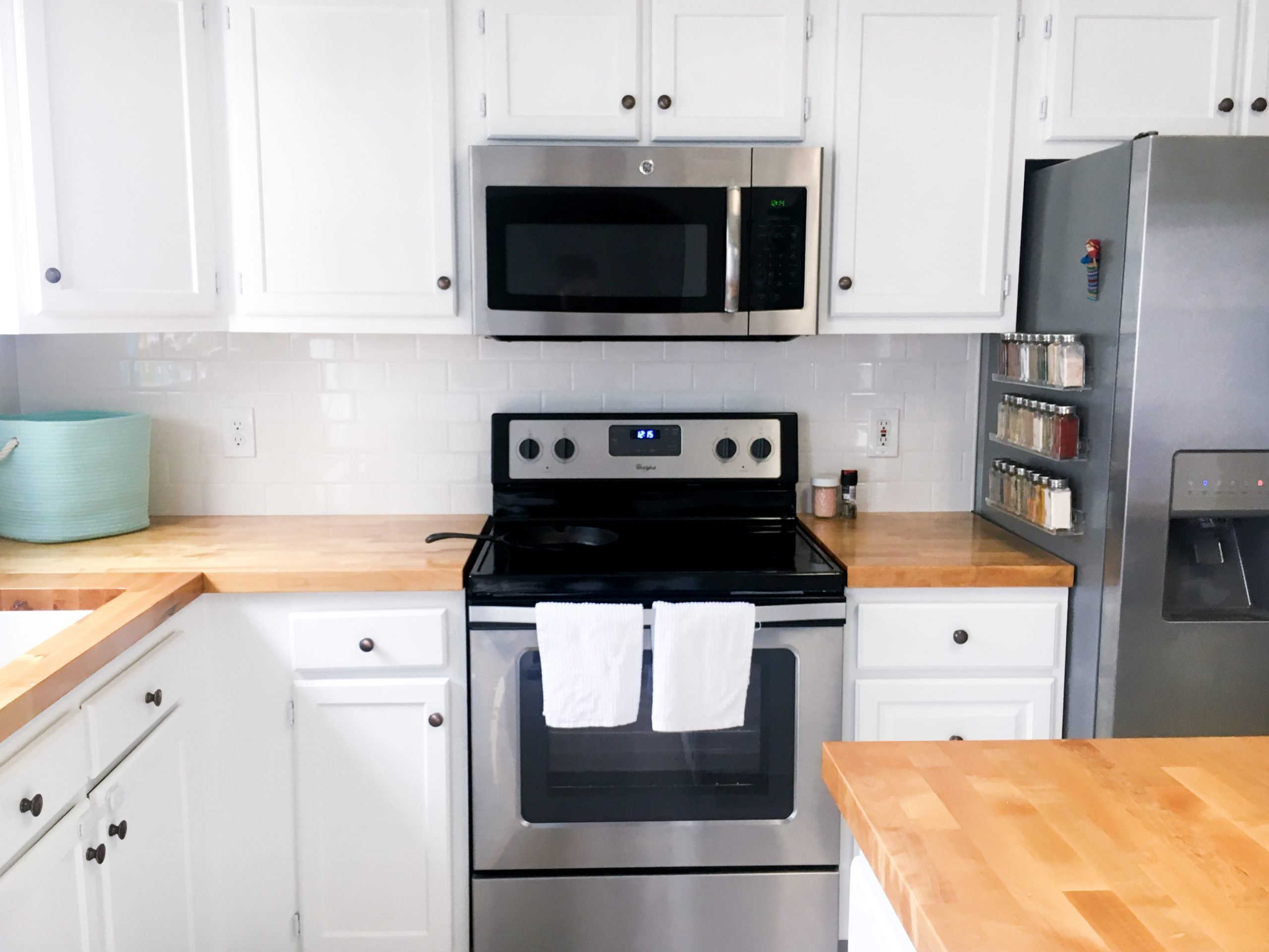 a diy mini kitchen remodel left this kitchen looking fresh and uncluttered. white cabinets, butcher block counters, stainless appliances, and subway tile bnacksplash.