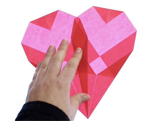 step by step folded paper window heart tutorial. a hand demonstrates the folding process
