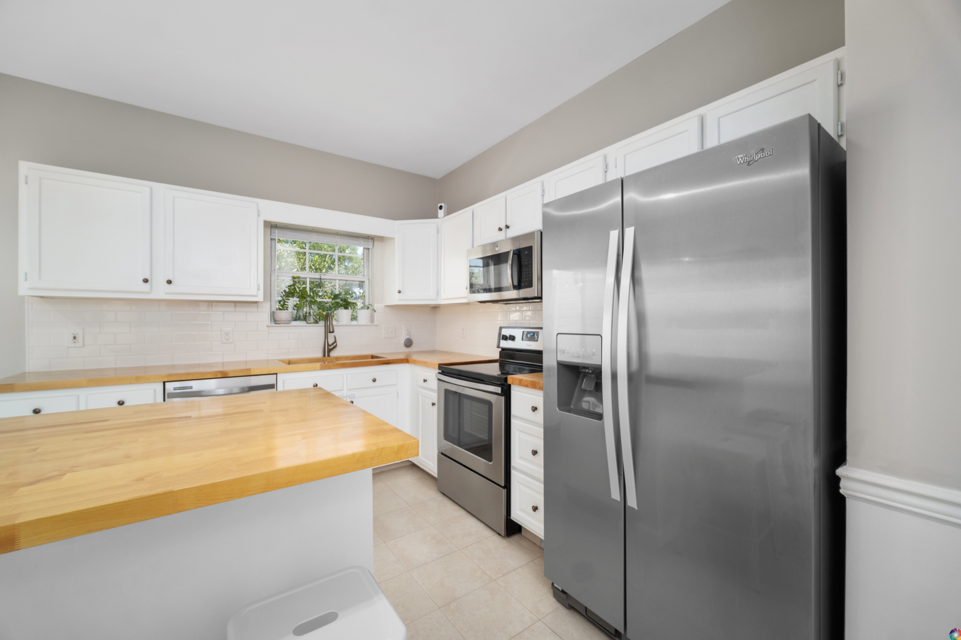 bright and airy kitchen remodel - white cabinets and butcher block counters with subway tile backsplash, stainless steel appliances