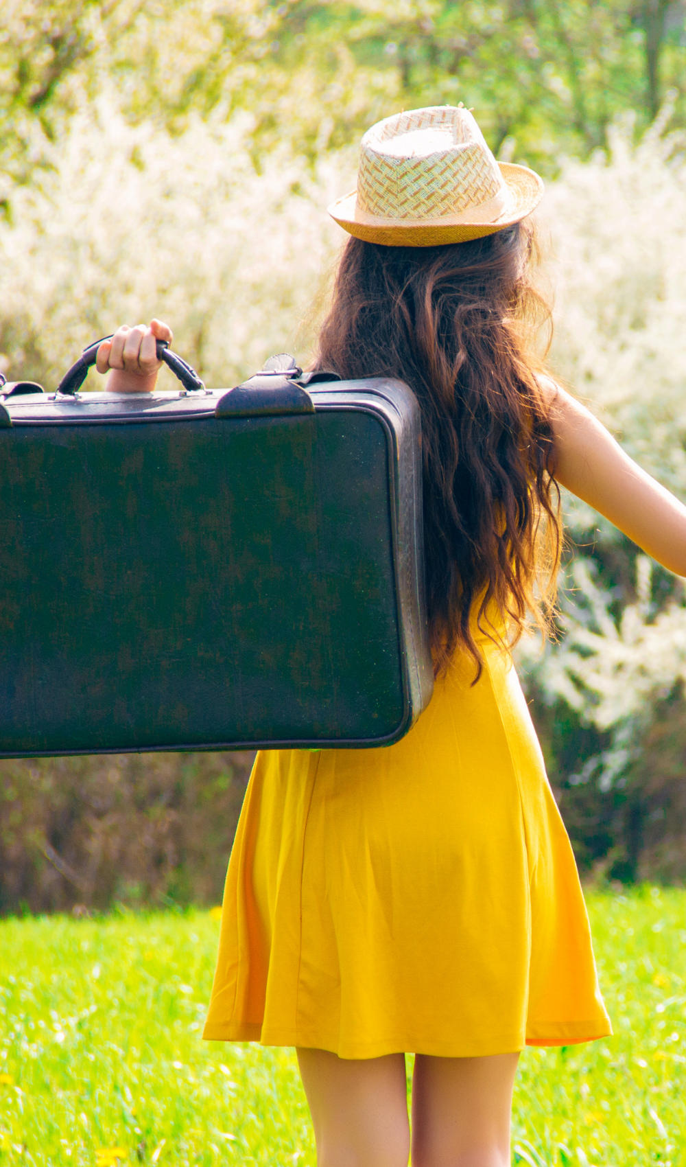 woman in a yellow dress and a hat walking away holding a suitcase over her shoulder