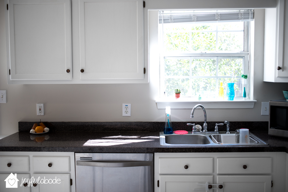 black kitchen counters, white cabinets, sink, looking out toward the backyard through the window