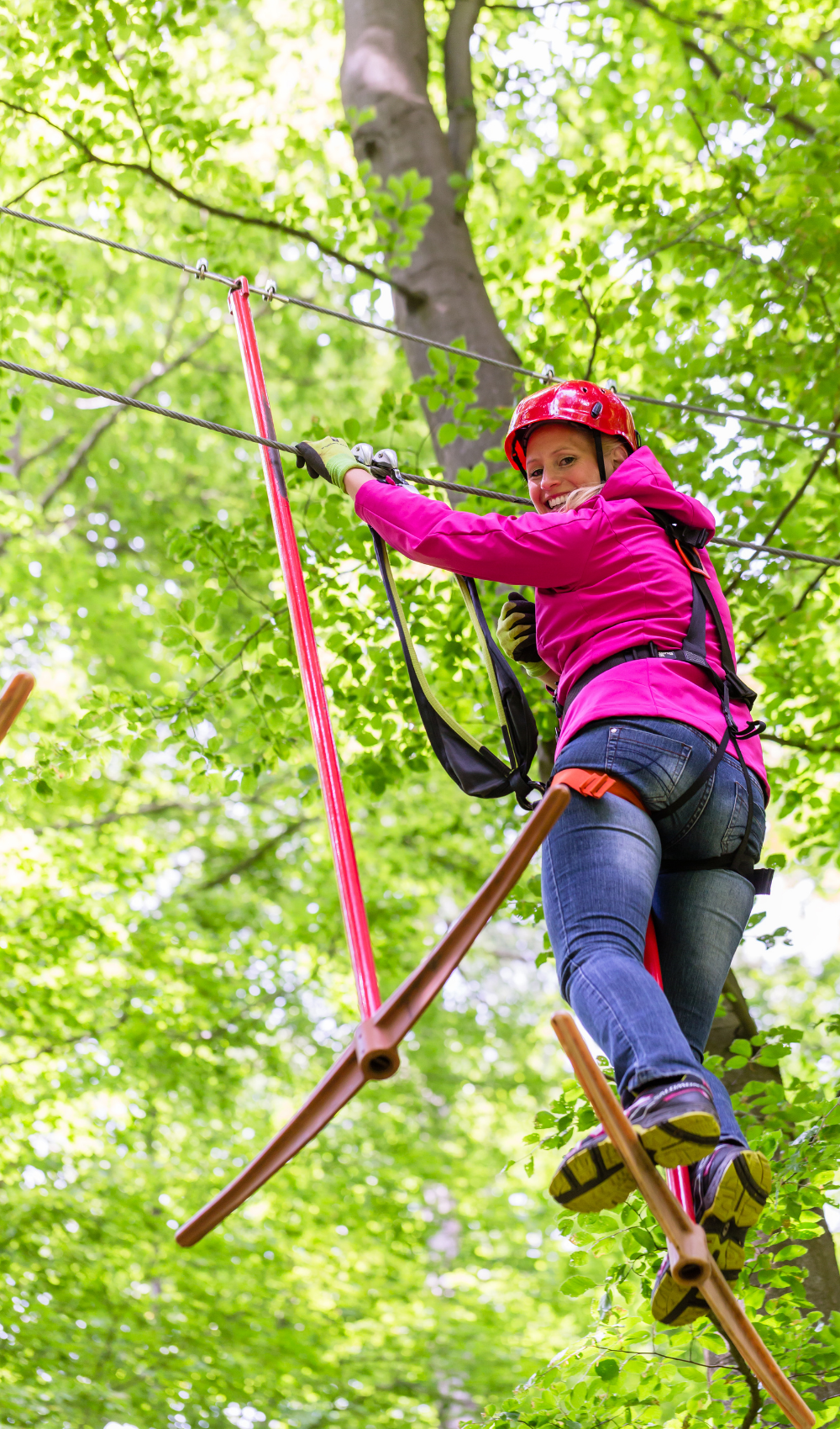 woman smiling on a ropes course alone