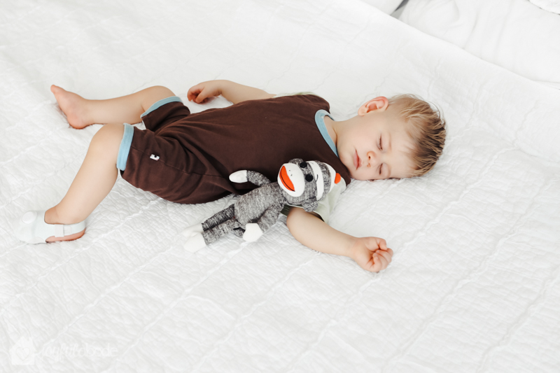 sweet baby taking a nap with his monkey wearing owlet baby care monitoring sock - coupon code, sleep tips for new parents