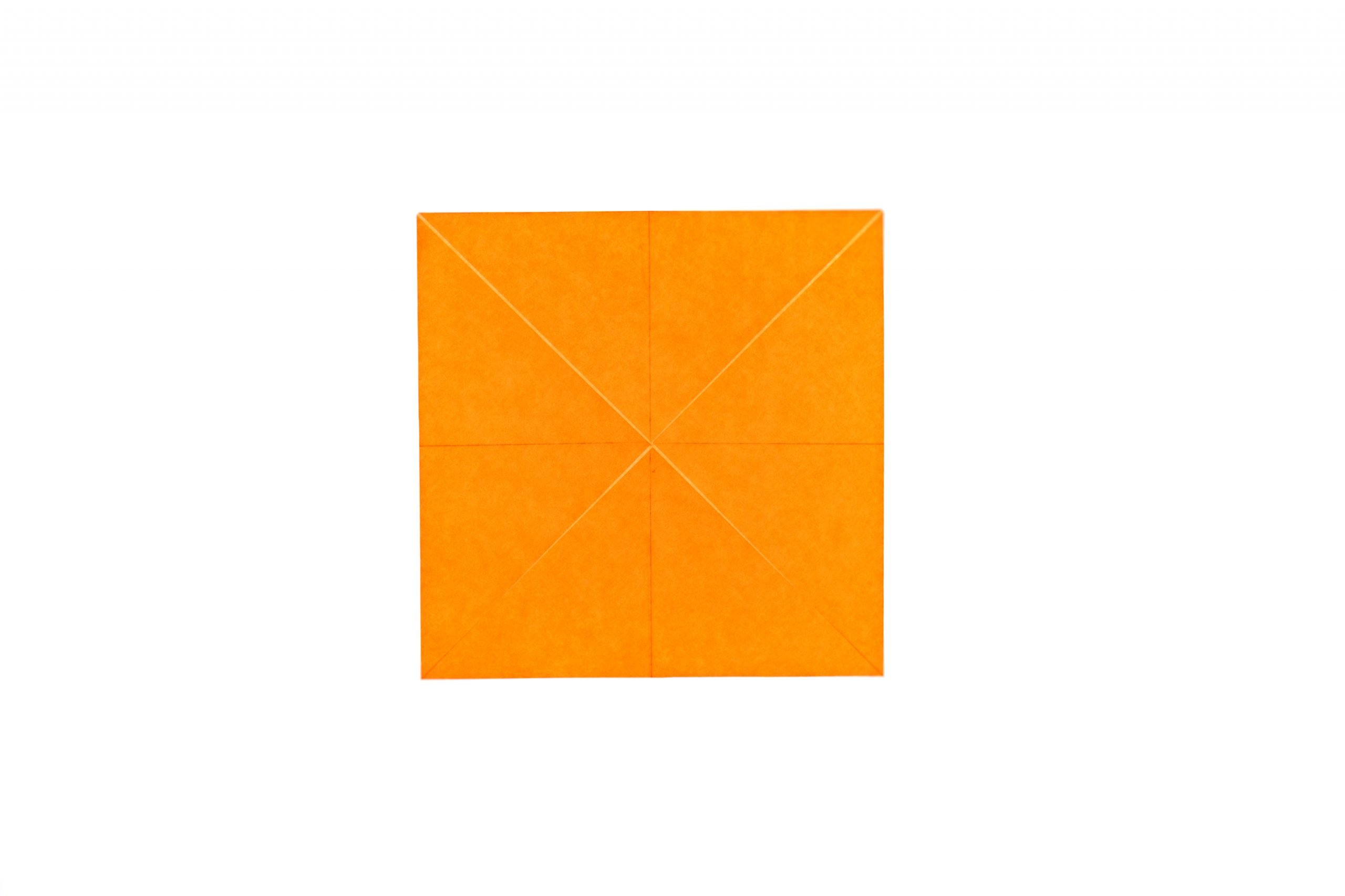 orange square of kite paper with corners folded in to the center