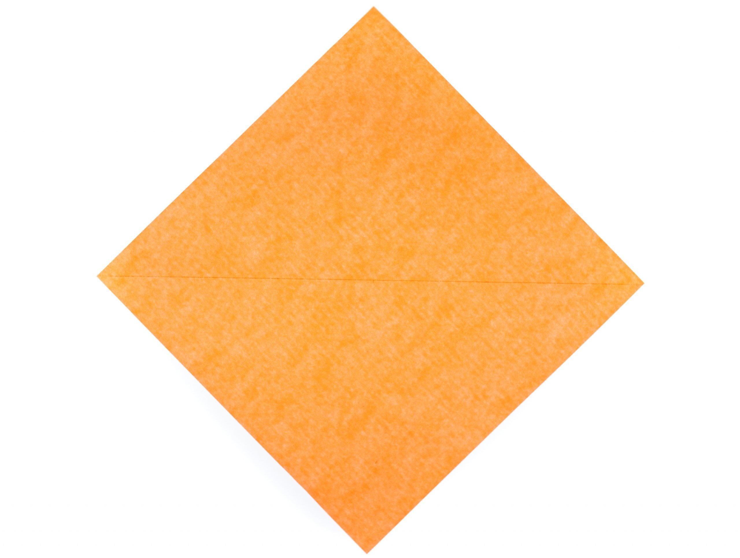 orange kite paper square with diagonal crease
