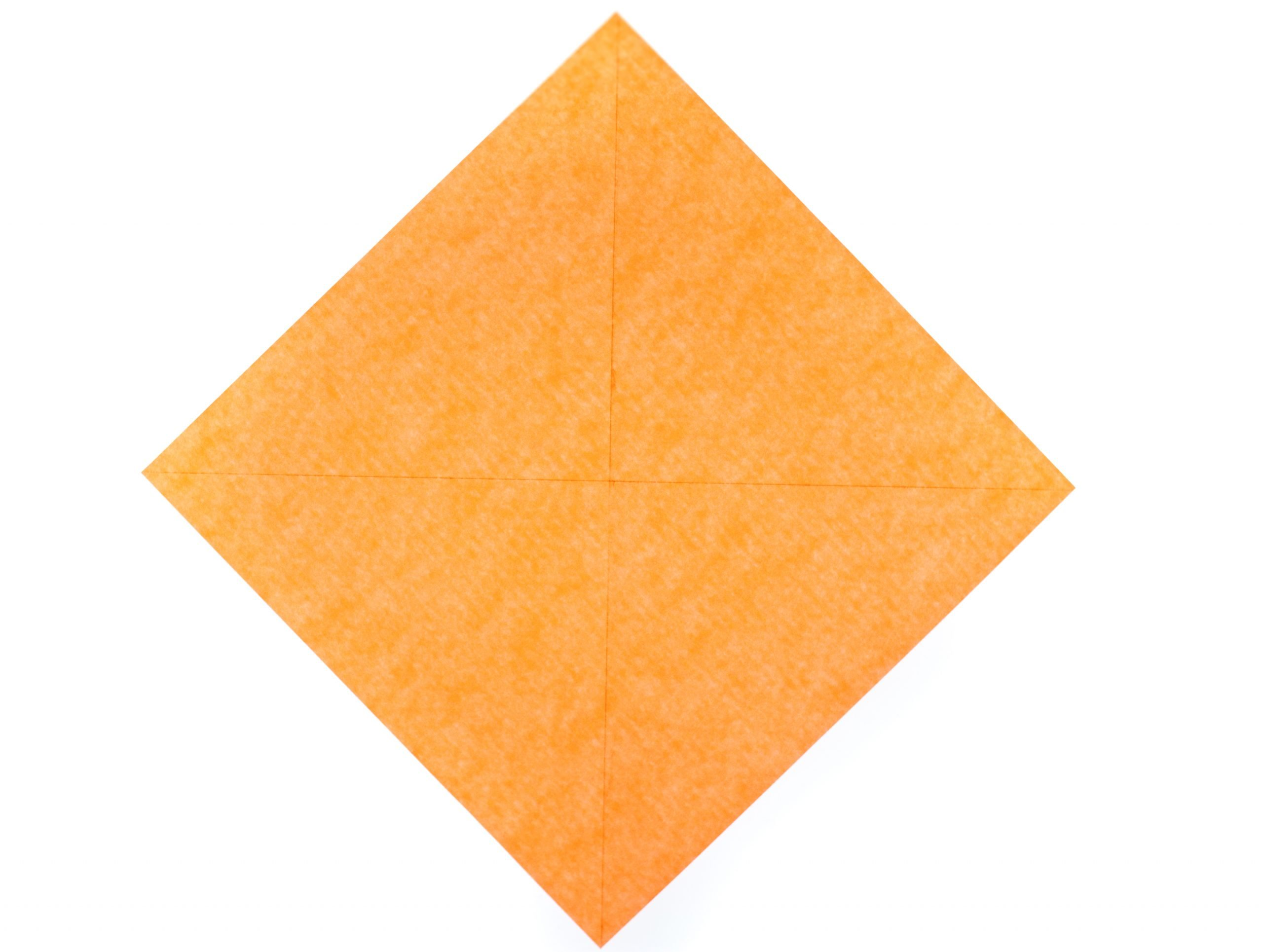 orange translucent paper square with two diagonal creases