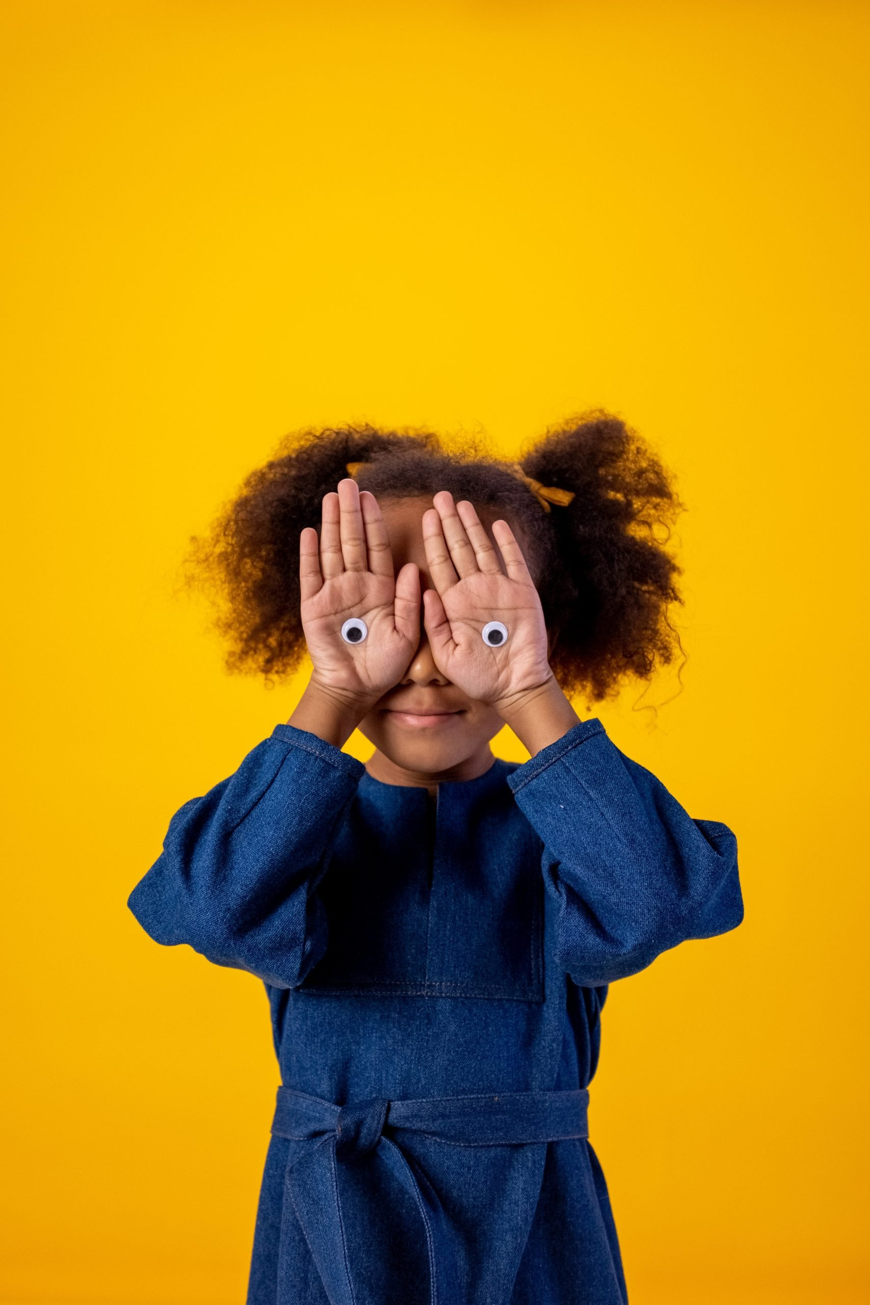 a child in a blue dress with natural hair in pigtails covers her eyes with her hands, palms out, with googly eyes stuck to her palms.