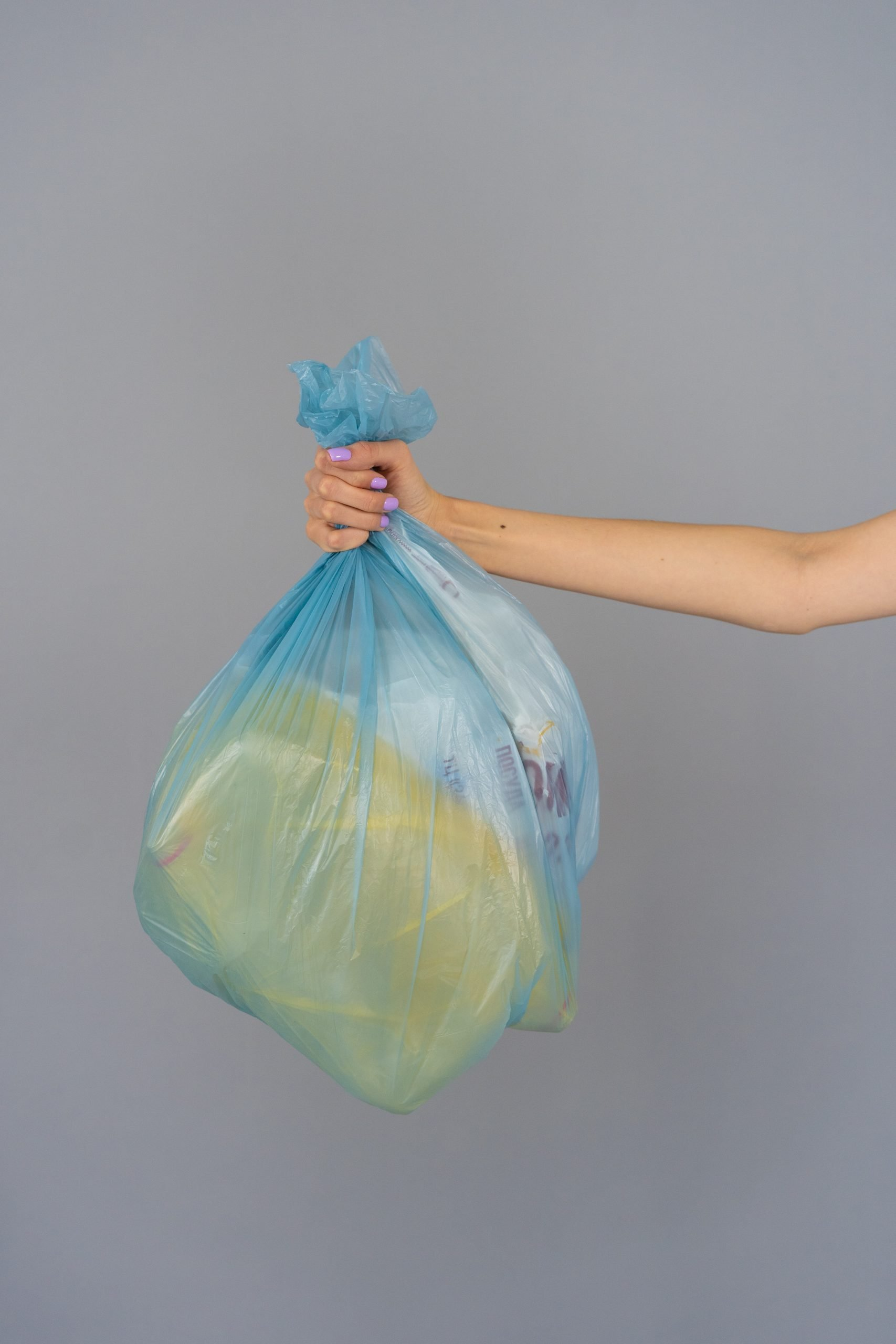 outstretched arm with hand holding a blue bag of trash.