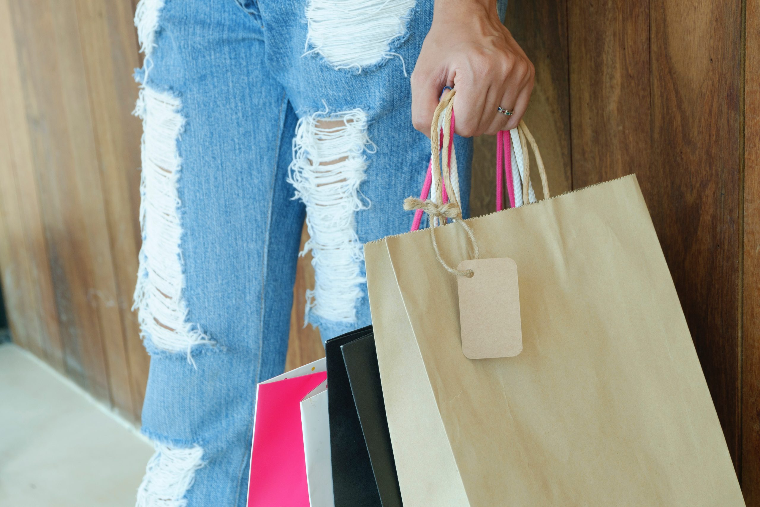 a person in distressed jeans holding shopping bags.