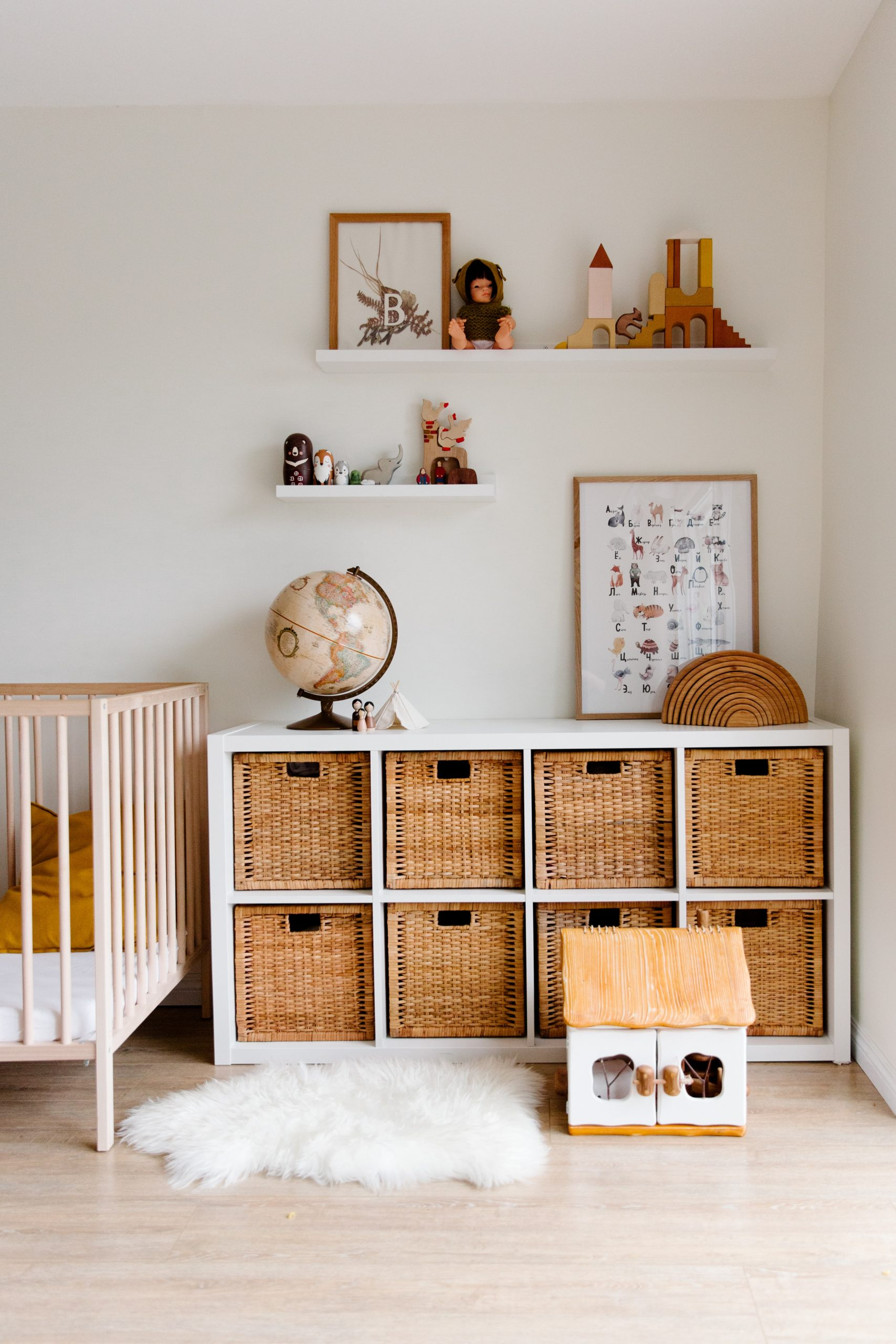 organized child's bedroom with bins inside of a white cubby shelf