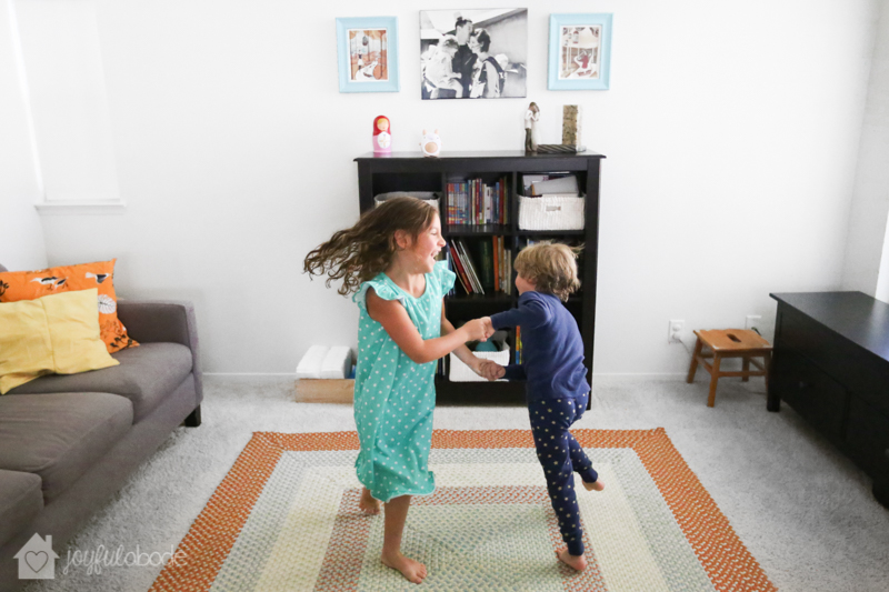 kids dancing in the living room to music playing on their soundbub bluetooth speaker for kids