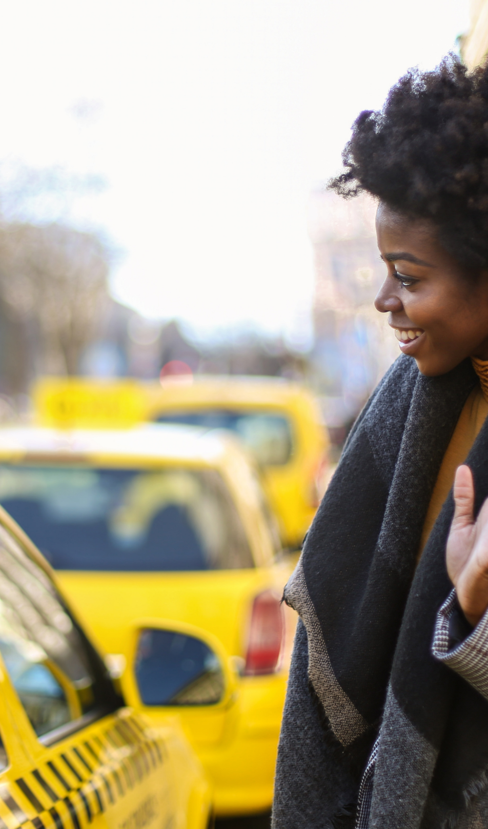 woman raising her hand to call a taxi
