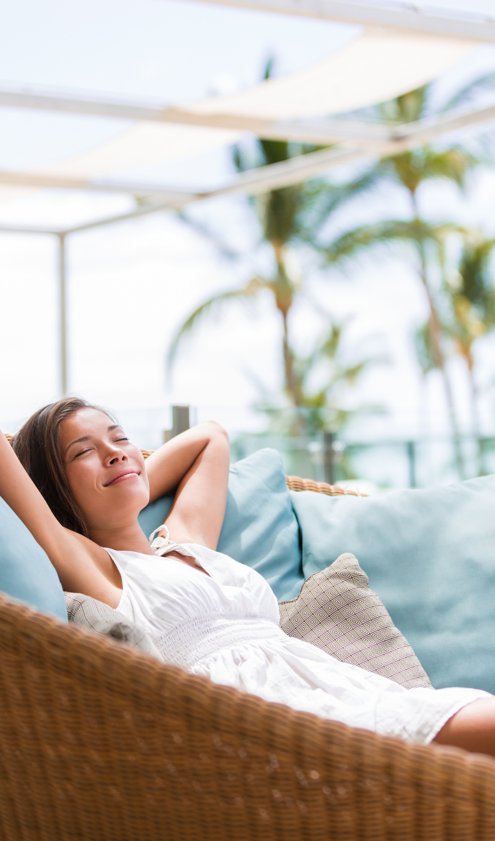 smiling woman napping in a comfortable couch on a porch in a tropical location